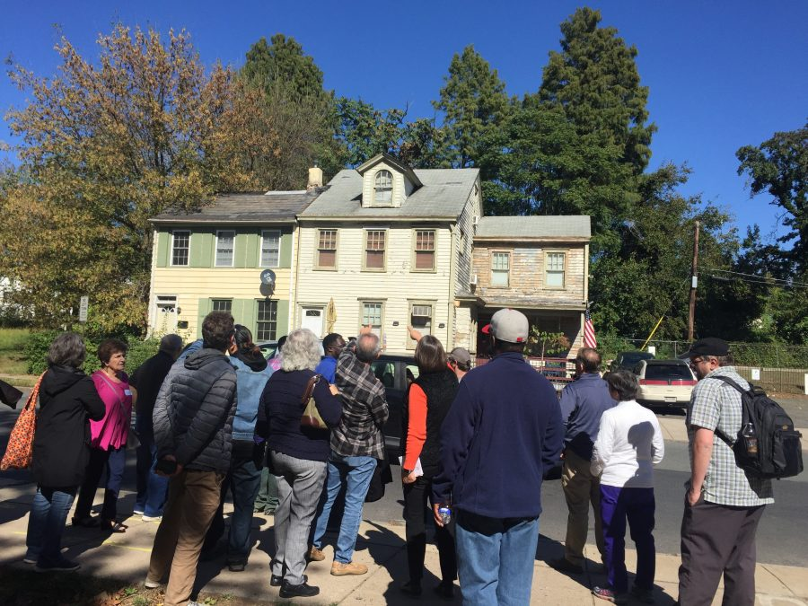This is a color photograph of a group of people taking walking tour looking at historic buildings in Trenton, NJ. They are pointing toward one of two buildings sided in wood in the background.