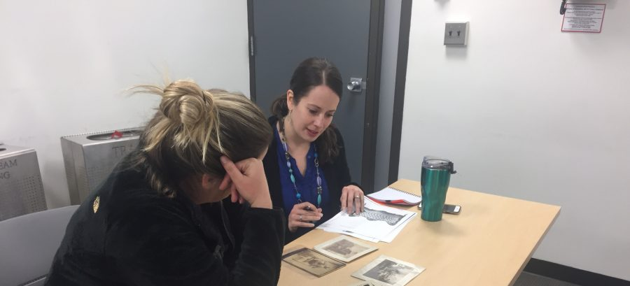 This is a photograph of two students in a classroom looking at and talking about historic photographs together.