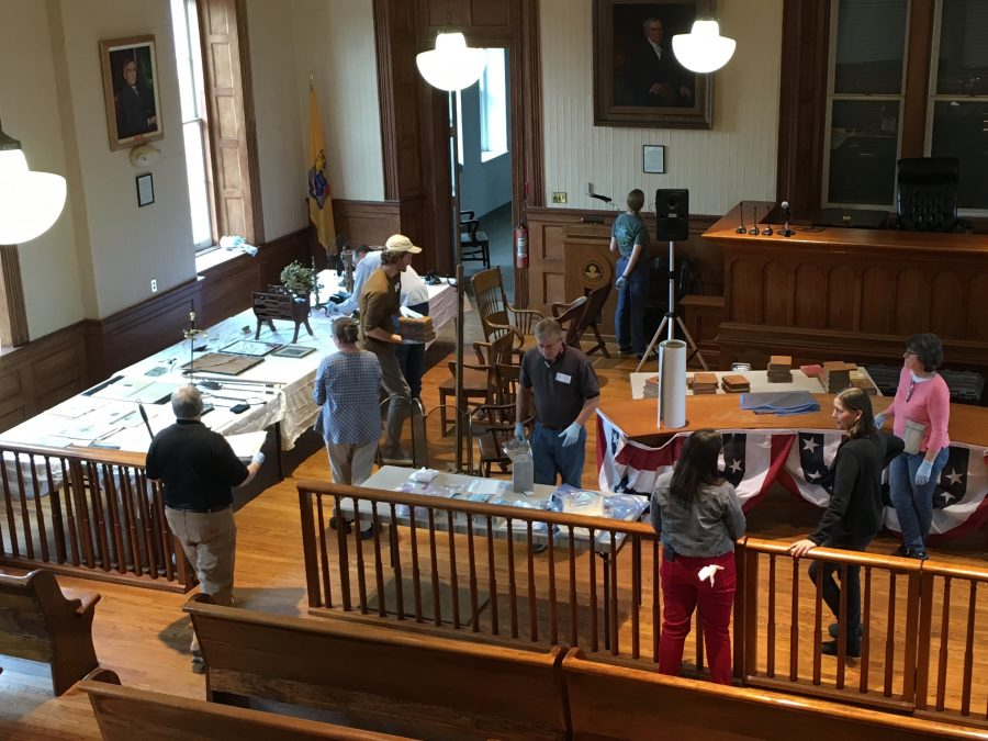This is a photograph of four people cleaning artifacts inside a historic courtroom. Photo take from balcony.